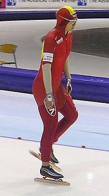 Une patineuse en combinaison rouge, portant également un brassard blanc et des lunettes. Elle se tient sur le pied droit et est complètement debout.