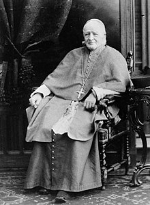 A seated elderly man in Roman Catholic priest's vestments.