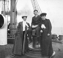 Two women standing and one man sitting aboard a ship