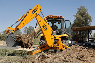 Backhoe - Rear view of a JCB 3CX showing the backhoe being employed to remove a tree stump. Horizontal stabilizers are deployed to prevent the vehicle from tipping laterally when the arm is extended.