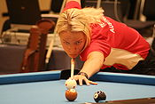 Woman shooting pool while hunched over a table