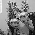 Kerstmis nadert jonge vrouw toont grote kerstballen, Bestanddeelnr 918-5563.jpg