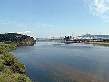 Un fiume vasto e tranquillo in una limpida giornata d'autunno.  Condomini ed edifici in costruzione sono visti in lontananza.