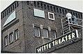 Kunstenaar Pieter Kooistra bevestigd een ornament van zijn kunstwerk aan de gevel van het Witte Theater in IJmuiden. NL-HlmNHA 54050081.jpg