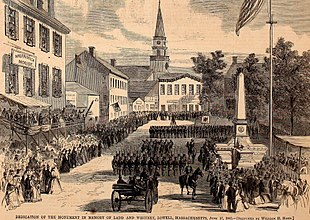 A black and white lithograph of a city square, a stone obelisk and large formations of militia soldiers in dark uniforms parading past the monument