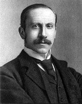 En moustachioed mand i en mørk tredelt dragt