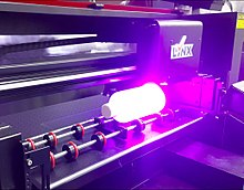 A Lynx ULTRA 64 flatbed UV printer with a rotary attachment printing on a bottle.