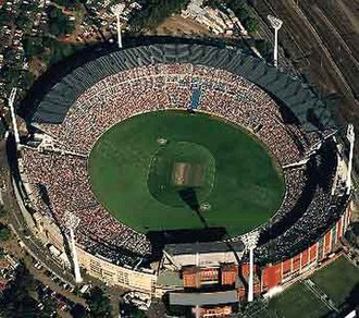 In 1992 the West Coast Eagles became the first non-Victorian team to win an AFL premiership. Pictured is the Melbourne Cricket Ground in 1992 where the grand final was held. The stadium is pictured as configured for a cricket match, note the visible pitch and absent goal posts. MCG stadium.jpg