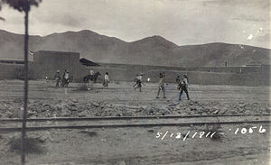 A group of men wearing sombreros walking along a dirt road between a railroad track and a line of buildings. Dated 5/13/1911.