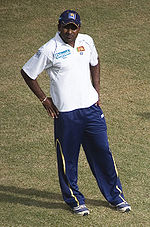 A man in a white T-shirt and dark blue cap, wearing dark blue tracksuit trousers.