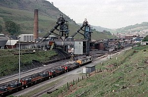 Ebbw Vale Steelworks - 10 May 1989, and a British Railways Class 37 diesel locomotive hauls a train of rolled steel coils up the Ebbw Valley towards the tinplate works, passing the recently closed Marine Colliery in Cwm, Blaenau Gwent. Marine was a former EVSICC colliery, and this picture epitomises the integrated nature of coal and iron ore with steel making