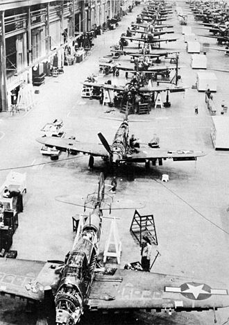 """Sacramento McClellan Airport - Bell P-39 Repair Line. To step up its delivery of Speedy Bell P-39 """"Airacobra"""" fighter airplanes to American pilots in the South Pacific, the Army Air Forces Air Service Command put American production line methods to work in its repair docks at McClellan Field, California. Two and one-half million dollars worth of airplanes were overhauled by civilian Air Service Command workers at Sacramento, California prior to being sent against the enemy."""