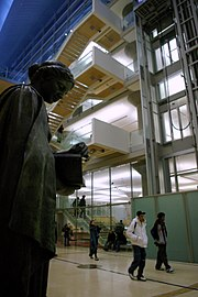 Patrons walking towards door in modern lobby with 19th C. bronze sculpture of Minerva by Jakob Fjelde on left