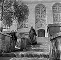 Monnik, vermoedelijk een franciscaan, in habijt op de trappen voor de kerk van d, Bestanddeelnr 255-0443.jpg
