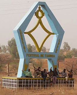 Children sit under the monument to the Festival of Tahoua