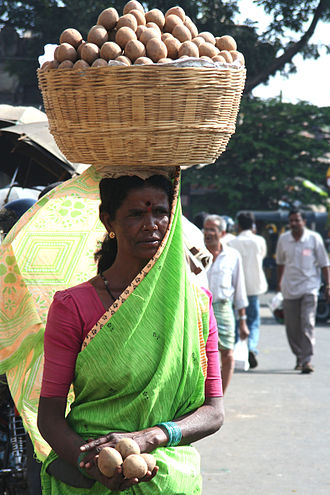 Head-carrying - Sari-clad woman in Mysore, India, balancing a basket of chikku (or sapota; a type of fruit) on her head.