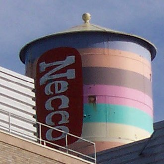 Central Square, Cambridge - The New England Confectionery Co. water tower, built 1927, was painted in 1996 to resemble a roll of Necco Wafers, but repainted to a new design in 2004 by Novartis.