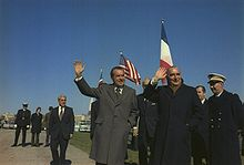 Two men in suits stand to the right, with uniformed military officers nearby. Both men are waving and smiling.