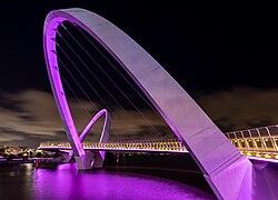 Un pont, tenu par une arche inclinée, éclairé de violet.