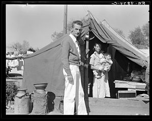 The Harvest Gypsies - Tom Collins was the manager of the Kern migrant camp in 1936 when Dorothea Lange took this photograph of him with a migrant mother in the background.