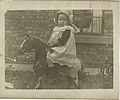 Postcard, sepia, showing a small girl aged about 3 years ? wearing a bonnet, a white pinafore with crochet insertions, seated on a large toy horse. Brick wall and part of a sash window can be seen in (15406994263).jpg