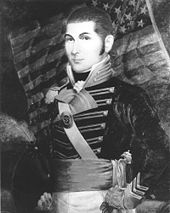 portrait of O'Bannon staning in a dress uniform with an American Flag in the backgroun