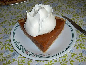 Cream - A slice of pumpkin pie topped with a whipped cream rose