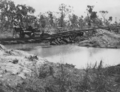 Queensland State Archives 6410 Flood Damage to Rail Track showing complete washaway leaving rails suspended Location Unknown c 1955.png