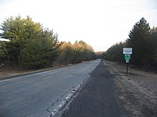 "A straight two-lane road between evergreen trees. A signpost at right has signs reading ""Cameron County"" and ""Gibson Township"" and ""Building-Sewage Permits Required Flood Plain Regulations Enforced"" and ""10"". In the distance is a yellow sign showing a T-intersection at right."