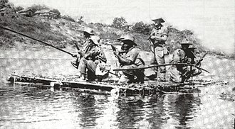 A raft on a river. A man with a rifle stands in the centre, surrounded by other men kneeling on one knee.
