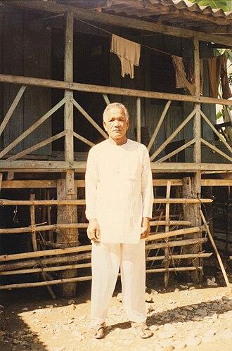 Rabha tribe - A Rabha gentleman, in front of his house in a forest village, Gayarkata, Jalpaiguri