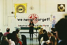 "A seated crowd facing a standing woman. Behind her is a table with flowers. Above the table is a large banner with the text, ""We never forget!"" along with the IWW name and globe logo. A variety of United Auto Workers logos are visible on the wall in the background."
