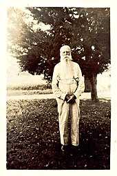 A black and white image (c. 1900s) of an elderly man with white hair and a long beard dressed in a long-sleeved and suspenders standing in front of a tree.
