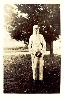 A black and white image (c.1900s) of an elderly man with white hair and a long beard dressed in a long-sleeved and suspenders standing in front of a tree.