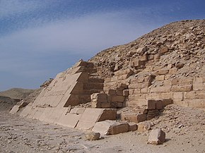 Bottom foreground shows the white limestone casing that remains at the lowest layers of the pyramid. Roughly dressed blocks of various sized can be seen behind the casing. The amount of rubble increases with height.