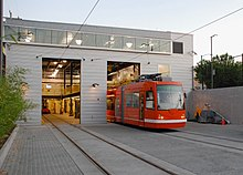 A red streetcar entering a gray, metal building that is lit from the inside.