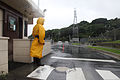 Security guard Atsushi Shimabukuro waits at the gate of U.S. Marine Corps Base Camp Smedley D. Butler in Okinawa, Japan, Oct. 28, 2010, to check identifications and talk to drivers about weather conditions 101028-M-VG363-002.jpg