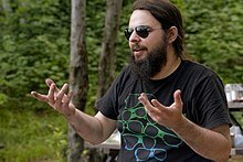 McGrath gesticulates with both hands while looking to the left. He wears aviator sunglasses, a black T-shirt with a sunglasses graphic, and has a long, brown beard. He is in an outdoors, camping setting.
