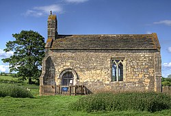 A small chapel seen from the south, with a bellcote at the left, a door and a single window