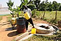 Staff member lifting water from a shallow well (approx. 3 meter deep) at St. Peter's Rambula Mixed Secondary School (5050689129).jpg