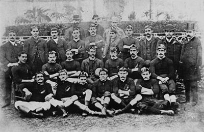 A black and white photograph of 27 men arranged in four rows posing for a team shot. The players in the front rows are in black jerseys and white shorts, while those not playing are in suits to the back.