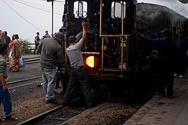 Two men behind a steam locomotive