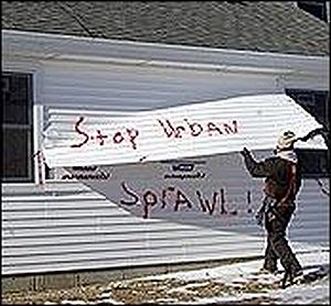"Ecotage - ""Stop Urban Sprawl"" is spray-painted on a multimillion-dollar house to protest the development. Mansions in the United States are a frequent target by the ELF."