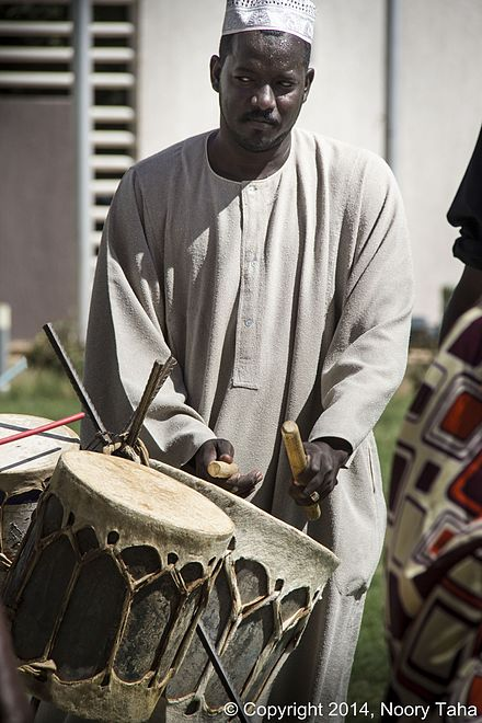 A man playing traditional Sudanese drums. Sudanese Traditional music instrument.JPG