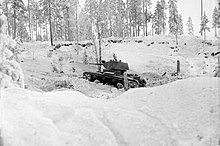 A Soviet light tank, seen from its left side, is described by the Finnish photographer as advancing aggressively in the snowy forested landscape during the Battle of Kollaa.