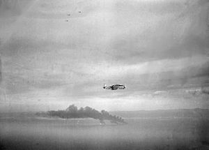 Cam Ranh Bay - A U.S. Navy TBM Avenger flies past three Japanese oilers burning in Cam Ranh Bay, 1945
