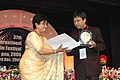 "The noted film star, Aparna Sen giving away the Golden Peacock Award for the best film to the Director of the film ""The Old Barber"" (China) Mr. Hasi Chaolu during the closing ceremony of the 37th International Film Festival.jpg"