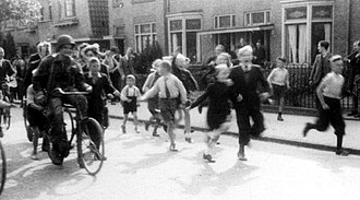 Theodore Bachenheimer - The Netherlands, Sept 18, 1944. An American paratrooper riding a bicycle into the town of Nijmegen, followed by a group of excited children. The unknown U.S soldier was identified as Theodore Bachenheimer.