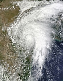 A satellite image depicting a well-developed tropical cyclone moving across Mexico and Texas.