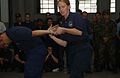 U.S. Coast Guard Lt. Peggy Gross (right) and Lt. j.g. Luis Gonzalez (left), both with the USCG International Training Division, demonstrate the proper restraining hand grip to handcuff a suspect to the 041004-F-RL328-041.jpg